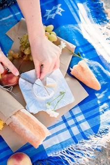 Letni piknik romantyczny z owocami, serem, winem, pieczywem, winogronami, brzoskwinią. światło z pierwszych promieni słońca.