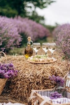 Letni piknik w lawendowym polu. kieliszki wina, kosz piknikowy, przekąski i bukiety kwiatów na stogu siana wśród krzewów lawendy. miękka selektywna ostrość.