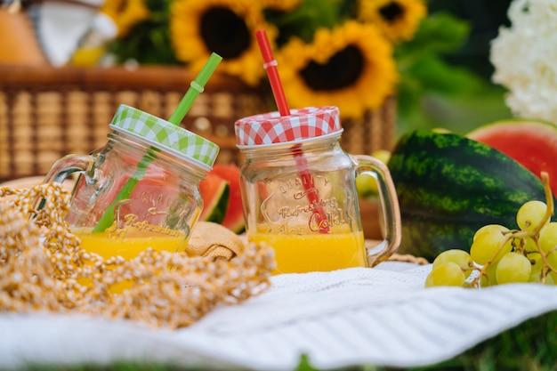 Letni piknik w słoneczny dzień z arbuzem, owocami, bukietem kwiatów hortensji i słoneczników.