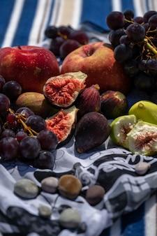 Letni piknik z figami, winogronami i jabłkami. morze i kratę na plaży?