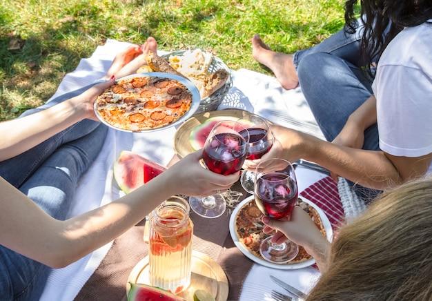 Letni piknik z przyjaciółmi na łonie natury z jedzeniem i napojami.