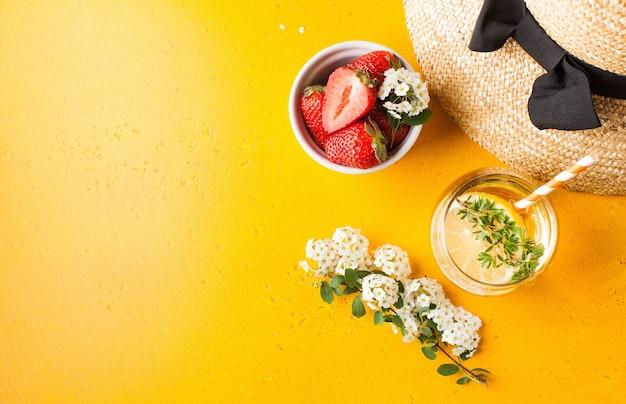 Letni płaski słomkowy kapelusz orzeźwiający lemoniada dojrzałe truskawki w misce kopia przestrzeń