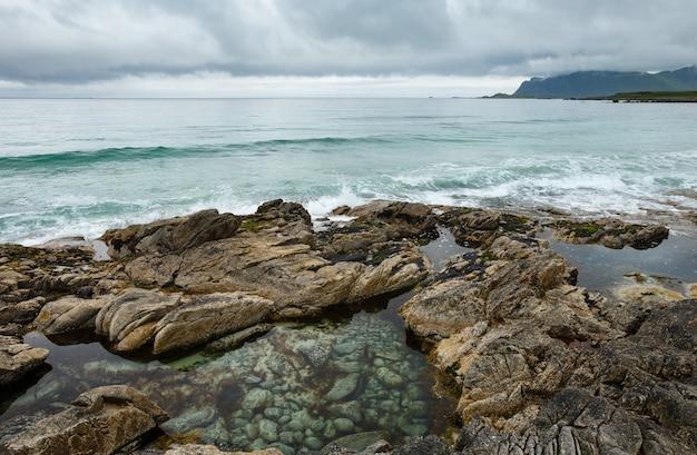 Letni pochmurny widok na plażę z basenem pośrodku kamieni