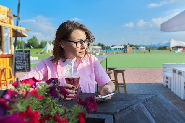 Letni portret dojrzałej kobiety z drinkiem i smartfonem, kobieta odpoczywa w kawiarni na świeżym powietrzu przy użyciu telefonu komórkowego