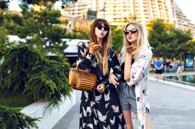 Letni portret dwóch stylowych całkiem najlepszych przyjaciółek, które świetnie się bawią razem, uśmiechają się i cieszą czasem na ulicy, eleganckie modne ubrania i okulary przeciwsłoneczne, szczęśliwa para, związki.