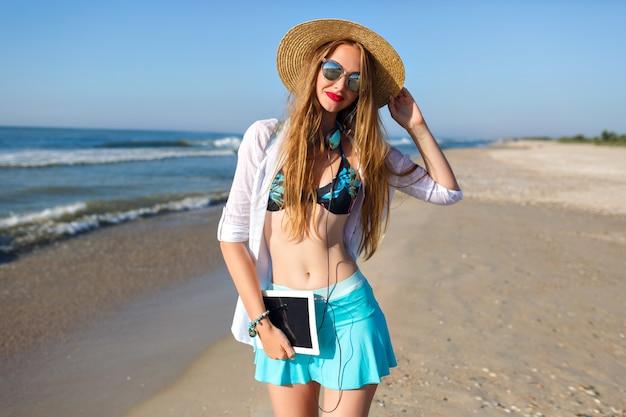 Letni portret ładnej blondynki pozującej na samotnej plaży w pobliżu oceanu, noszącej górę od bikini, jasną spódnicę i okulary przeciwsłoneczne, trzymając słuchawki i tablet, wakacyjny nastrój freelancera