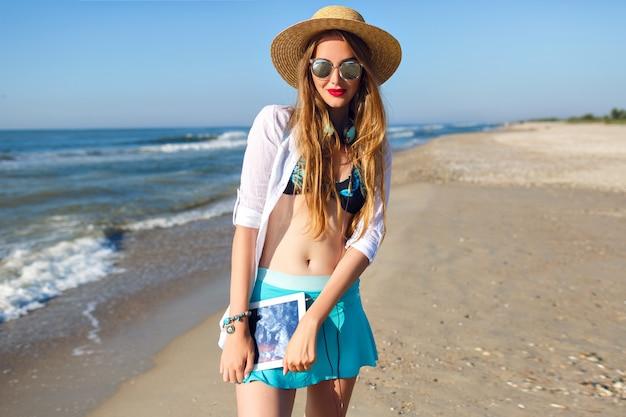 Letni portret ładnej blondynki pozującej na samotnej plaży w pobliżu oceanu, noszącej górę od bikini, jasną spódnicę i okulary przeciwsłoneczne, trzymając słuchawki i tablet