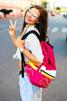 Letni portret miasta stylowego nastolatka, podróżującego samotnie z plecakiem, spędzającego miły dzień w nowym mieście, ciesz się wakacjami, nosząc plecak, okulary hipster i swobodny wygląd, radość, emocje