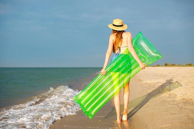Letni portret młodej kobiety relaksującej na plaży, trzymając duży materac z neonowym powietrzem, gotowy do morskiej zabawy, wakacyjny relaksujący nastrój.
