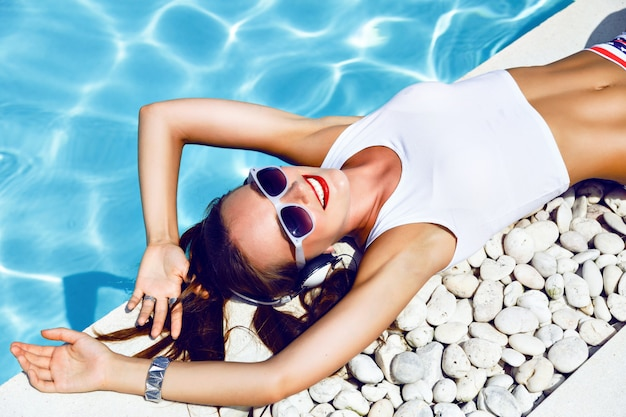 Letni portret mody młodej dziewczyny sexy dj leżącej w pobliżu basenu, noszącej seksowne mini szorty z gwiazdami w okularach przeciwsłonecznych w stylu vintage, uroczą fryzurę i jasny makijaż, słuchając muzyki na słuchawkach.