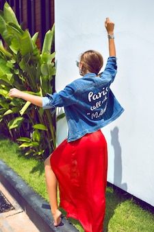 Letni portret mody o oszałamiająca elegancka dziewczyna pozuje na zewnątrz w tropikalnym kraju, ubrana w elegancką luksusową sukienkę i modną dżinsową kurtkę, tańczy i dobrze się bawi.