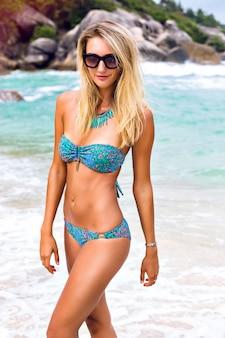 Letni portret mody oszałamiającej kobiety z opalonym, dopasowanym seksownym ciałem, noszącej jasną biżuterię bikini i okulary przeciwsłoneczne, pozuje na plaży tropikalnej wyspy z czystą, błękitną wodą.