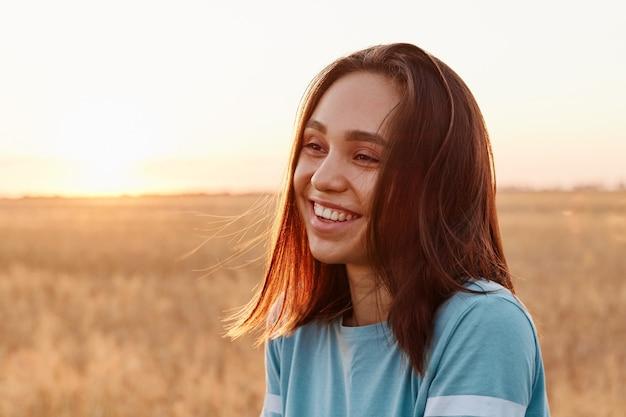 Letni portret roześmianej szczęśliwej kobiety na świeżym powietrzu, cieszącej się ciepłym słońcem, ubrana w niebieską koszulkę, o ciemnych włosach, odwracająca wzrok z uśmiechem zębów, wyrażająca szczęście.