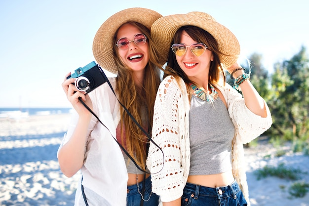 Letni portret styl życia szczęśliwych najlepszych przyjaciółek siostrzanych dziewcząt pozujących na plaży, słoneczne jasne kolory, słomkowe kapelusze i okulary przeciwsłoneczne, trzymając rocznika aparat fotograficzny, dobrze się bawić.