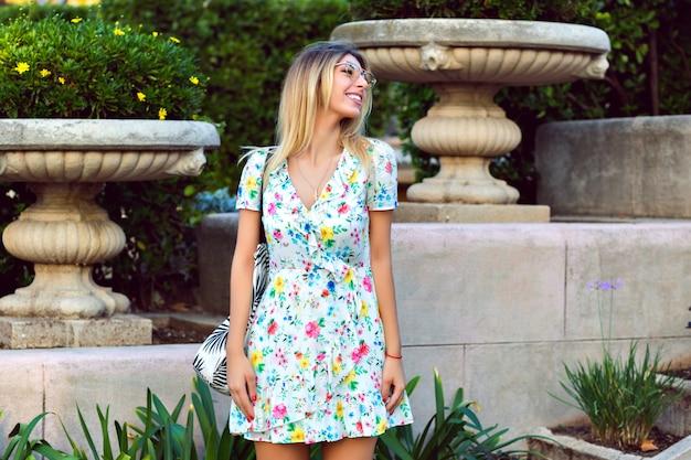 Letni portret stylowej szczęśliwej wspaniałej blondynki stylowej kobiety na sobie lekką elegancką modną kwiecistą herbatę i pozuje w starym europejskim parku, podróżujący nastrój.