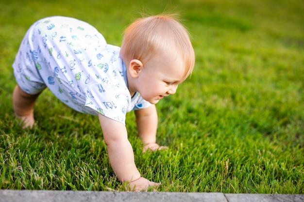 Letni portret szczęśliwego śmiesznego chłopca na zewnątrz na trawie w polu dziecko uczy się raczkować