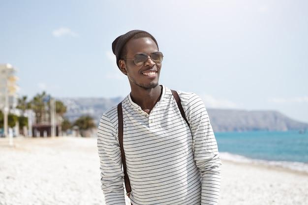 Letni portret uśmiechniętego szczęśliwego ciemnoskórego mężczyzny w modnych nakryciach głowy i okularach przeciwsłonecznych spędzających słoneczny dzień na plaży miejskiej, spacerując, bawiąc się i ciesząc się morzem, wyglądając beztrosko i zrelaksowany