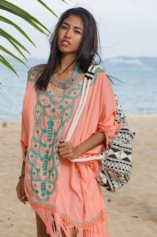 Letni portret uśmiechniętej ładnej azjatyckiej kobiety w różowym stylowym stroju plażowym, siedzącej na piasku w pobliżu palmy, błękitnego oceanu. biżuteria, bransoletka i naszyjnik.