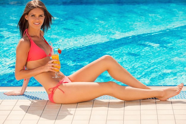 Letni relaks. atrakcyjna młoda kobieta w bikini siedząca przy basenie z koktajlem i uśmiechnięta