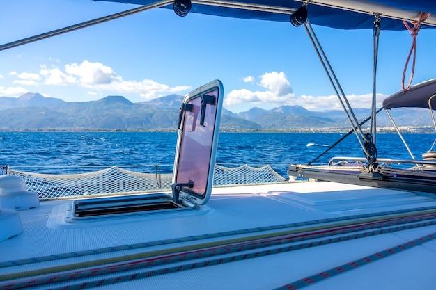 Letni słoneczny dzień na pokładzie jachtu żaglowego. olinowanie i maszt. widok na pagórkowate wybrzeże