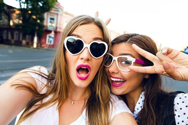 Letni słoneczny obraz dwóch sióstr najlepszych przyjaciółek, brunetki i blondynki, zabawy na ulicy, robienia selfie, noszenia śmiesznych okularów przeciwsłonecznych w stylu vintage, jasnego, stylowego makijażu długich włosów