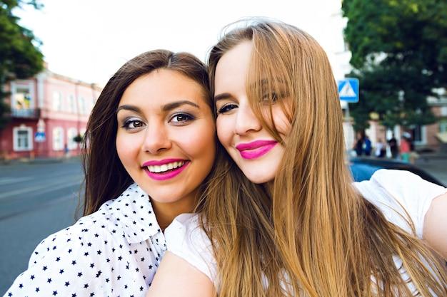 Letni słoneczny obraz dwóch sióstr najlepszych przyjaciółek, brunetki i blondynki, zabawy na ulicy, robienie selfie, jasny, stylowy makijaż, długie włosy