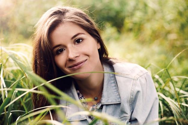 Letni słoneczny portret dziewczyny siedzącej na trawie
