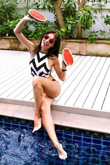 Letni słoneczny portret szczęśliwa brunetka kobieta odpoczywa w pobliżu basenu, ciesząc się upalną pogodą, na sobie bikini i okulary przeciwsłoneczne, czas wakacji.