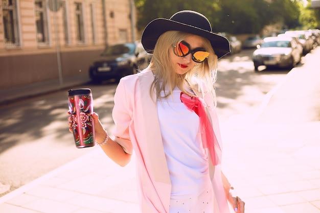 Letni słoneczny styl życia moda portret młodej stylowej hipster kobiety spaceru na ulicy, ubrana w ładny modny strój, pijąc gorącą latte