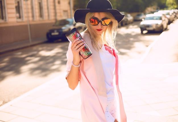 Letni słoneczny styl życia moda portret młodej stylowej kobiety hipster spaceru na ulicy, ubrana w ładny modny strój, pije gorąco