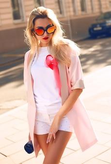 Letni słoneczny styl życia moda portret młodej stylowej kobiety hipster spaceru na ulicy, ubrana w ładny modny strój,