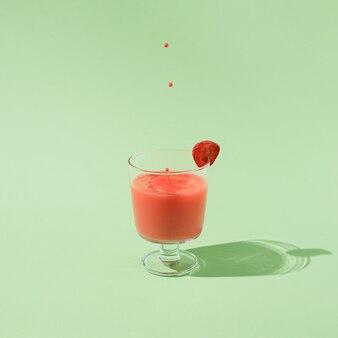 Letni sok truskawkowy z spadającymi kroplami na białym tle na zielonym tle. minimalna koncepcja abstrakcyjna. układ kwadratowy z miejscem na kopię