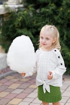 Letni spacer po parku rozrywki dziewczynka ze słodkim bawełnianym deserem