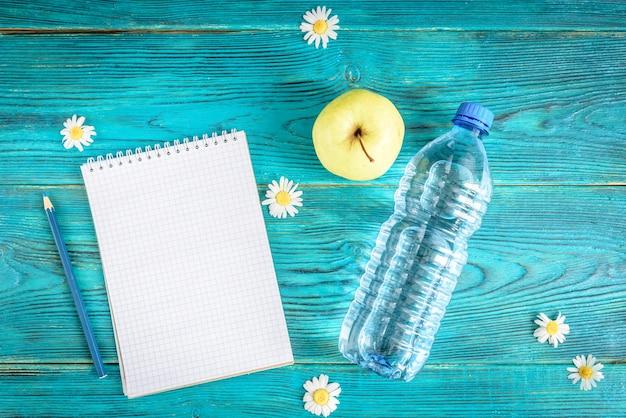 Letni stół roboczy z notatnikiem i kwiatami chamomiles na niebieskim drewnianym stole, leżał płasko