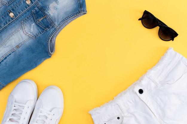 Letni strój: t-shirt w paski, jeansowe szorty i białe snickery.