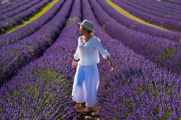 Letni styl portret uroczej kobiety w średnim wieku uśmiecha się i bawi się fioletowymi kwiatami lawendy