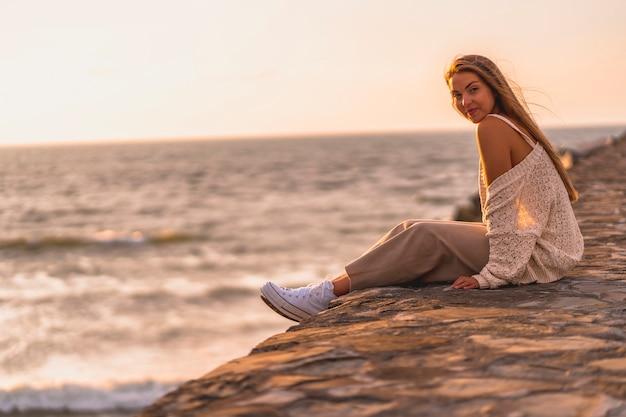 Letni styl życia, młoda blondynka rasy białej, siedząca nad morzem w białej bluzce i sztruksowych spodniach. cieszy się letnie popołudnie z morzem w tle