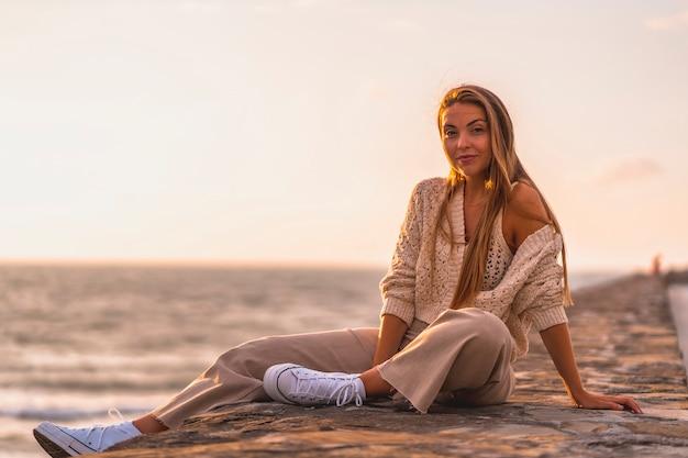 Letni styl życia, młoda blondynka rasy białej, siedząca nad morzem w białej bluzce i sztruksowych spodniach. w letnie popołudnie