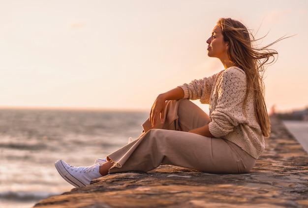 Letni styl życia, młoda blondynka rasy białej, siedząca nad morzem w białej bluzce i sztruksowych spodniach. z zamkniętymi oczami