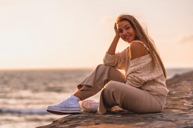 Letni styl życia, młoda blondynka rasy białej, siedząca nad morzem w białej bluzce i sztruksowych spodniach.