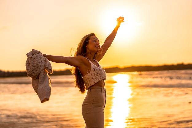 Letni styl życia. młoda blondynka rasy białej w białej bluzie z wełny na zachód słońca na plaży. cieszyć się i tańczyć nad morzem