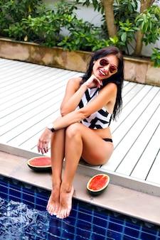 Letni styl życia na świeżym powietrzu obraz eleganckiej seksownej kobiety, pozującej w pobliżu basenu na wakacjach, ślubnego bikini w geometrycznym stylu i okularów przeciwsłonecznych, położyć arbuzy, szczęśliwe emocje.