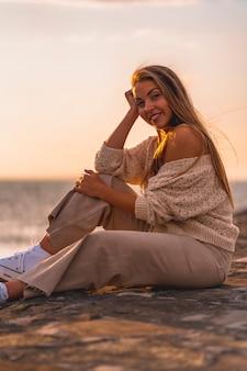 Letni styl życia, portret młodej blondynki rasy białej siedzącej nad morzem w białej krótkiej koszuli i sztruksowych spodniach.