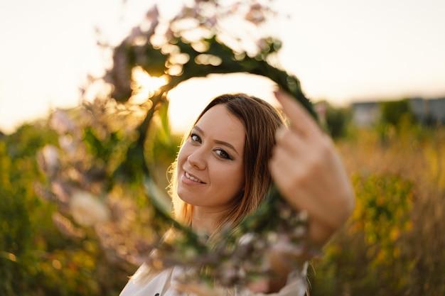 Letni styl życia portret pięknej młodej kobiety w wieniec z dzikich kwiatów wieniec na głowie