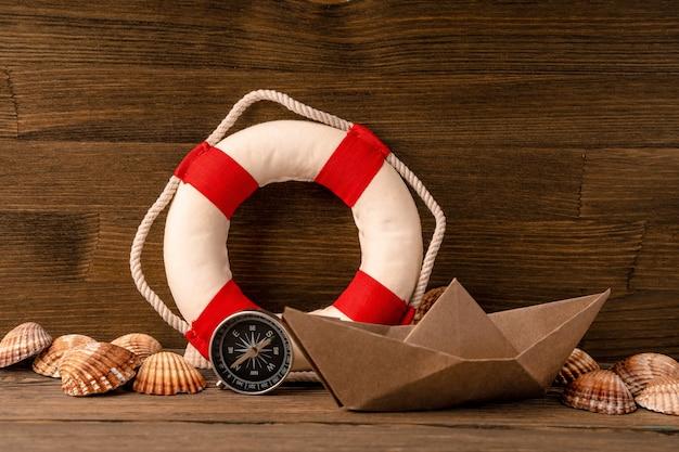 Letni sztandar morski. koło ratunkowe, muszle i papierowa łódź na drewnianym tle