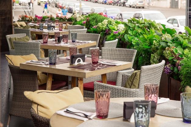 Letni taras kawiarnia, restauracja. stoły krzesła starannie ułożone i ustawione, aby służyć gościom.
