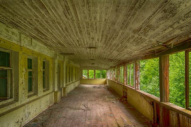 Letni taras na drugim piętrze w zrujnowanym domu w lesie.