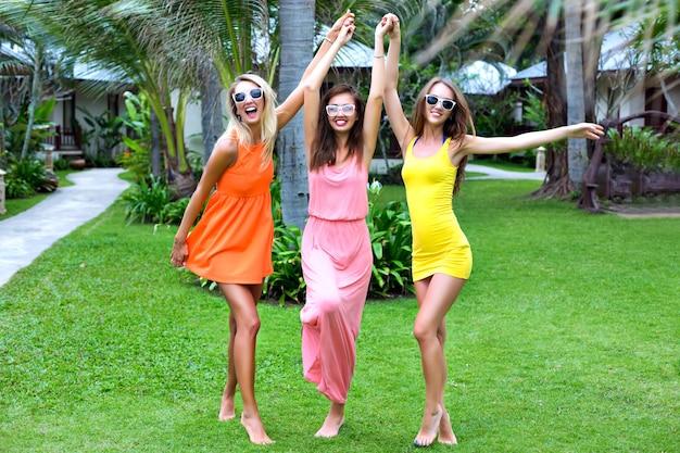 Letni tropikalny styl życia portret trzech szczęśliwych najlepszych przyjaciółek, które bawią się na świeżym powietrzu, noszą kolorowe seksowne sukienki, styl plaży na wakacje, egzotyczny ogród, modne okulary przeciwsłoneczne, relaks, radość