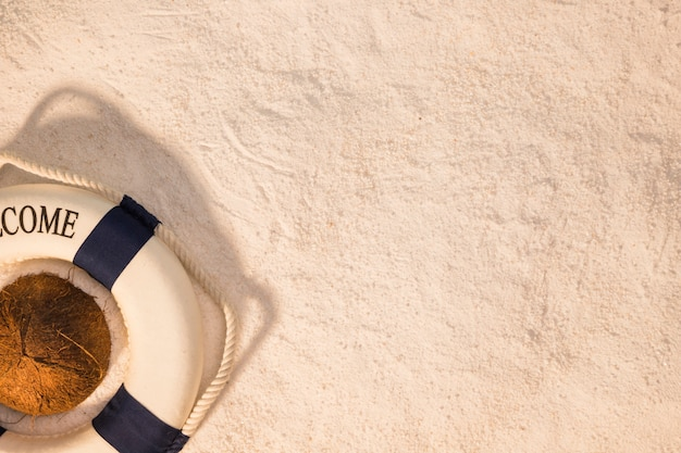 Letni układ kokosa i koło ratunkowe na piasku