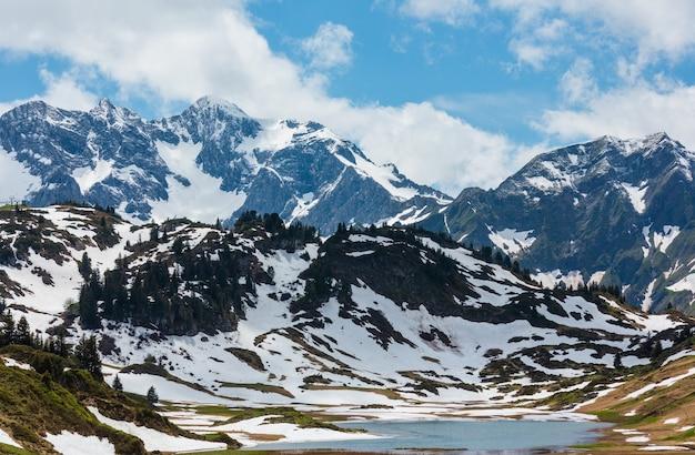 Letni widok na alpy na małe jezioro kalbelesee na przełęczy hochtannberg i łąka z rozmrażaniem śniegu (warth, vorarlberg, austria)